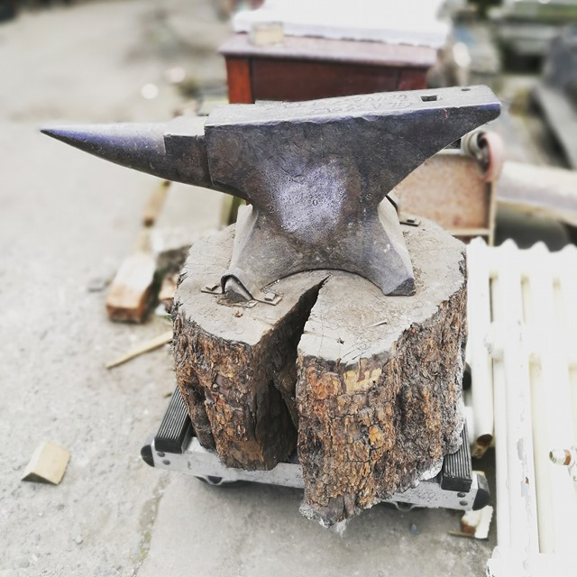 Anvil mounted on great bit of rough cut timber. Gallery Image