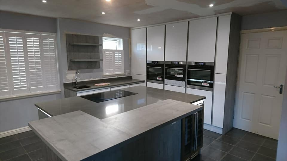 German handless design in Lanarkshire. Concrete effect island and breakfast bar, acrylic ultra gloss tall units, top spec AEG appliances and quartz worktops. Gallery Image
