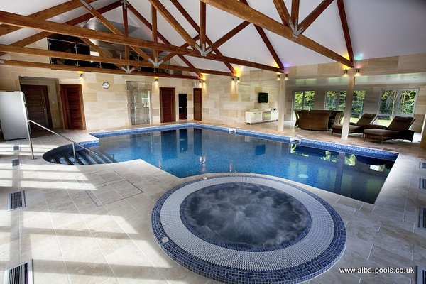 Skimmer pool with mosaic pattern liner, step unit and overflow spa pool. Gallery Image